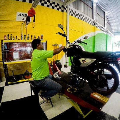 Hombre reparando motocicleta Ponce Racing